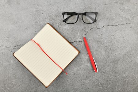 glasses with notebook on gray background. Office desk with business accessories. Top view.
