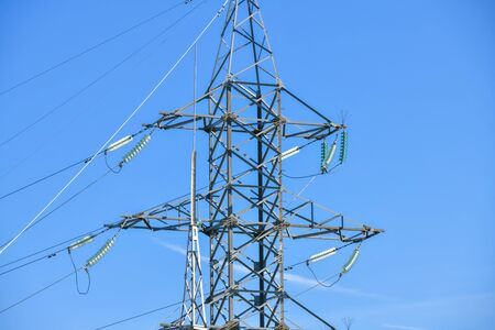 High voltage electricity pylons against perfect blue sky with white clouds. electric poles.
