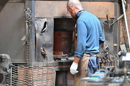 An experienced blacksmith works with open fire. A blacksmith extinguishes a flame in a forge with a spark firework, forges hot iron in a workshop. Stok Fotoğraf