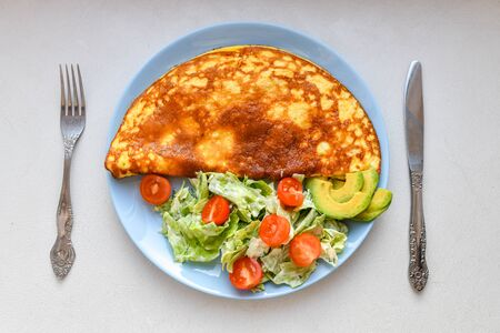 Fresh vegetables with scrambled eggs. on a round plate. Omelet with mushrooms. Stock Photo