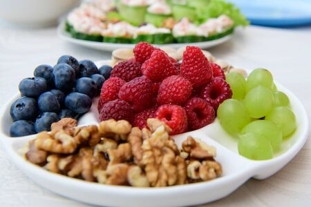 healthy nutrition, berries and nuts. wild strawberries, grapes, blueberries, walnuts, pistachios. Eco food concept. Mixed berries and nuts. DSLR royalty free image, healthy breakfast or snack option mixed berries with mixed nuts, on a white plate