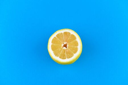 lemon on a blue background. half cut lemon. view from above. place to write. Lemon slices on a blue background. In summer, cool slices of orange slices. Lime, fruit, refreshing, yellow, vibrant, citrus, diet. Stok Fotoğraf