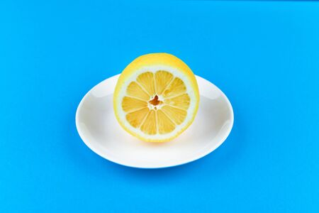 lemon on a blue background. lies on a white plate. half cut lemon. view from above. place to record. Lemon slices on a blue background. In summer, cool slices of orange. Lime, fruit, refreshing, yellow, vibrant, citrus, diet. Stock Photo