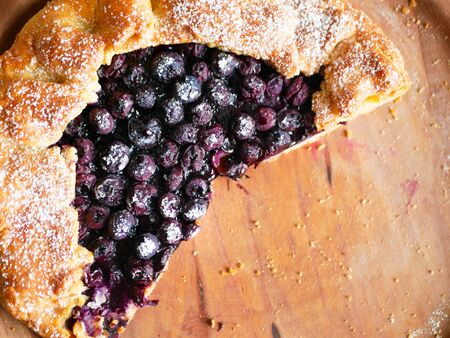 blueberry pie on a wooden plate. close-up. view from above. place for writing.