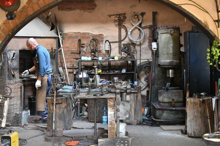 An experienced blacksmith works with open fire. A blacksmith extinguishes a flame in a forge with a spark firework, forges hot iron in a workshop.