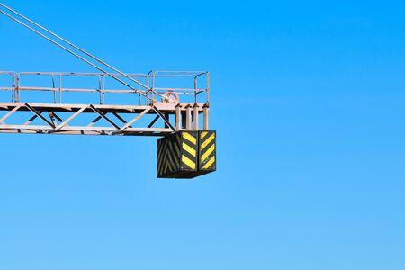 construction crane counterweight. High building construction site. Big industrial tower crane with blue sky amd cityscape on background. Concrete plates weight balance. Counterweight. Aerial drone view. Metropolis city development. .