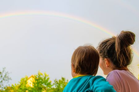Mom with a child looks at the rainbow. Mom and son on the background of motherhood. Look at the rainbow