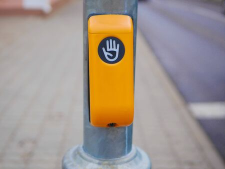 button to cross the street. Yellow button to safely cross the street on an iron pole. Stock Photo
