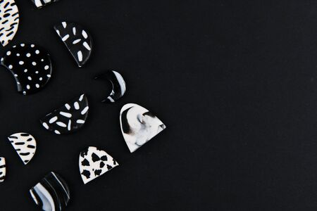 A product from polymer clay. Black and white polymer clay. Hand sculpting, product for earrings on a black background. View from above. Black and white jewelry earrings. Handmade polymer clay jewelry.