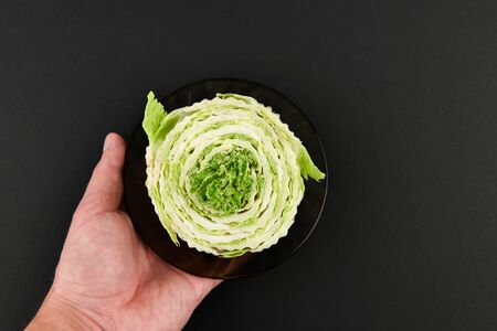 Peking cabbage in a hand on a black background. White Beijing cabbage. Permanent manager of fresh, dietary green and white Peking cabbage. In the shape of a cutout. Beijing cabbage in hand.