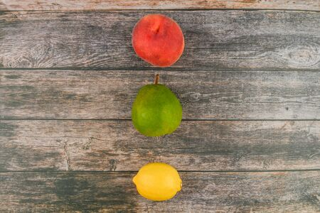 Peach, pear, lemon on a wooden background. Wooden blocks with the words Vitamin C, fresh fruits in the background, healthy food or diet concept. View from above. Place for writing