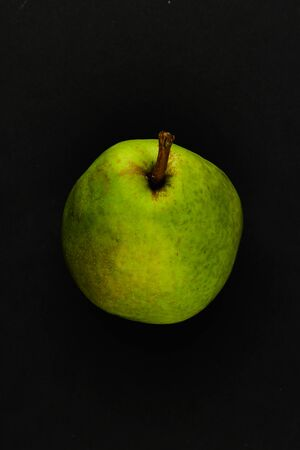 Pear on a black background. Fresh juicy pear on a black background. View from above. A place to write. In isolation. Cut out the background
