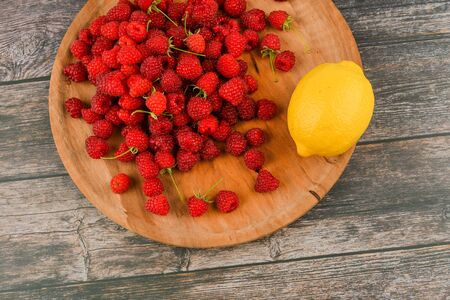 Raspberries with lemon on a wooden background. Wooden blocks with the words Vitamin C, fresh fruits in the background, healthy food or diet concept. View from above. A place to write