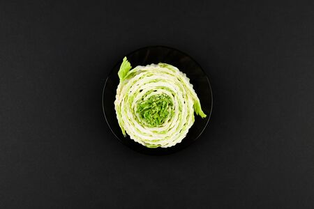 Beijing cabbage on a black background. Permanent manager of fresh, dietary green and white Peking cabbage. In the shape of a cutout. Beijing cabbage in hand.