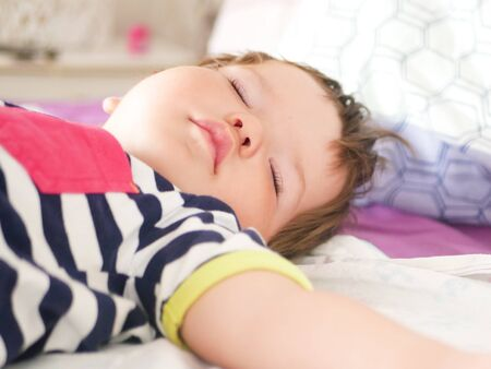 Childrens daytime sleep. Funny baby sleeping on the back of the bed at home. Children's day position. Healthy sleep. Arms outstretched during sleep. Foto de archivo