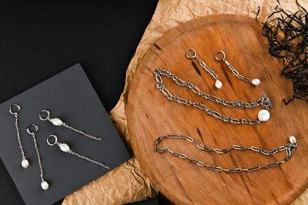 silver earrings on a chain. Close-up. Laid out on a wooden stand. View from above. The concept of jewelry and jewelry. Gifts for women. shopping. Handwork Imagens