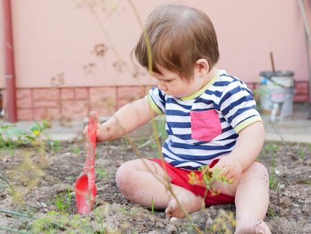 A boy plays with a spatula on the street. Baby boy and red shovel. Boy 0-1 years old.