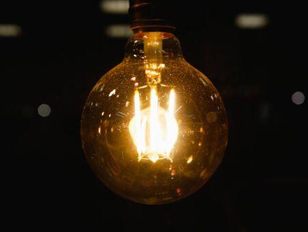 runde Glühlampe. Vintage stilisierte runde Wolframlampe. Leuchtend im Dunkeln, Nahaufnahme mit selektivem Fokus. Nahaufnahme. Dunkler Hintergrund. Hintergrund defokussieren