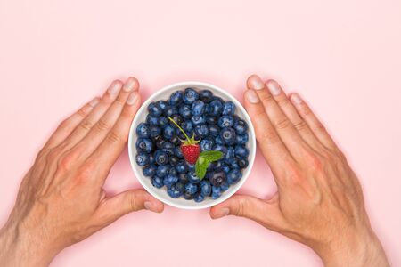 Blueberries in the hands. A man holds blueberries in his hands. Blueberries in a white bowl. Vitamins of nature. Berry nutrition. Place for writing. View from above Archivio Fotografico - 139821156