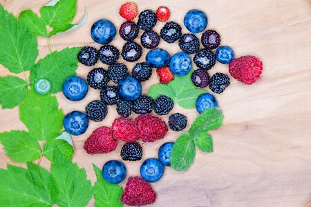 Wild berries on a wooden plate. Composition of three types of summer berries lying on a textured wooden plate. Top view on a wooden plate filled with many berries Zdjęcie Seryjne