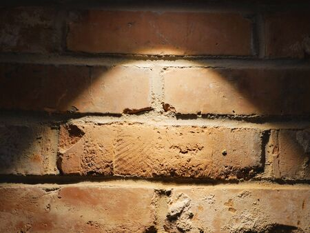The brick wall is lit by a lamp. Close-up. Brick wall for background. Brick backlight