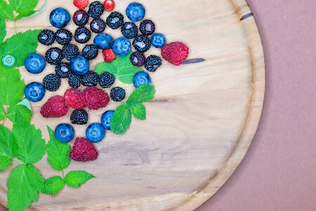 berries on a wooden plate. Composition of three types of summer berries lying on a textured wooden plate. Top view on a wooden plate filled with many berries. Wild berries