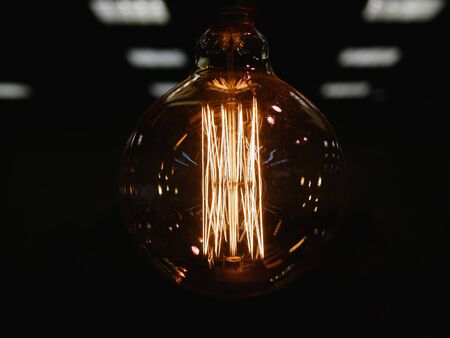 round incandescent lamp. Vintage stylized round tungsten lamp. Glowing in the dark, close-up photo with selective focus. Close-up. Dark background. Defocus background 스톡 콘텐츠
