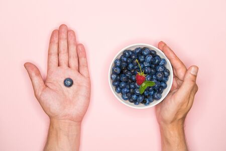 Blueberries in the hands. A man holds blueberries in his hands. Blueberries in a white bowl. Vitamins of nature. Berry nutrition. Place for writing. View from above