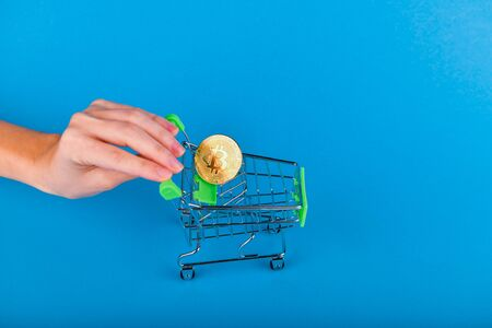 Bitcoin purchase concept. Bitcoin in the trolley, the hand pushes the shopping trolley where bitcoin is located. On a dark blue background