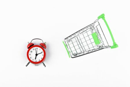 Shopping time concept. Online shopping concept. Cart and red retro alarm clock over white background. lack of time, waste of time, buying time, shopping concept, business concept