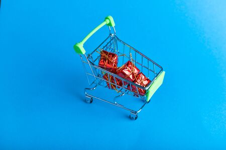 Christmas presents shopping concept. Basket and christmas accessories. Christmas basket with presents. Onlain shopping. On a blue background. place for writing