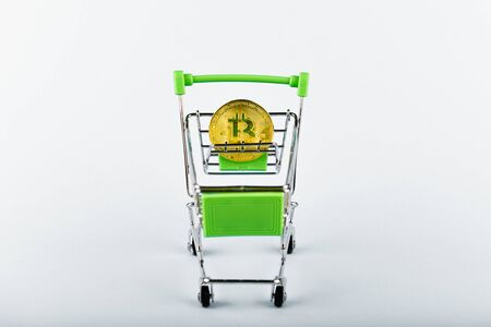 Bitcoin in the basket. On a white background, a place for an inscription. sell-out Stockfoto