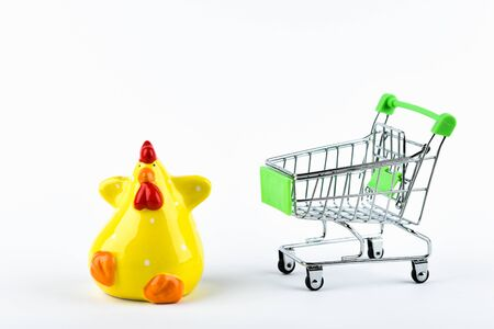 Buying chicken trading concept. Shop online. Basket and yellow chicken on a white background. Healthy eating concept. Business concept 스톡 콘텐츠
