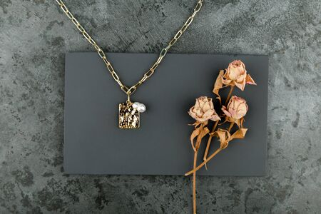 gold chain on a dark background. decorated with dried roses. handwork 스톡 콘텐츠