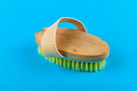 Wooden brush massager. massage wooden soft body brush with natural pile, worn on the hand, on a blue background, used in the shower to wash the body. Stock fotó