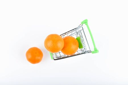 Mandarin trading concept. Online shopping concept. Cart and mandins over a white background. business concept. Healthy eating concept.