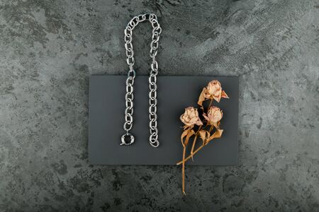 Silver chain on a dark background. decorated with dried roses. handwork 스톡 콘텐츠