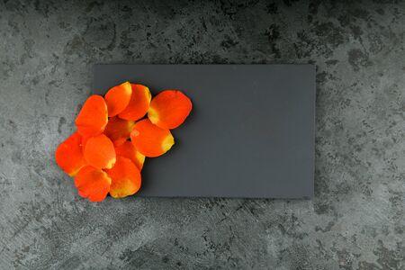 orange petals on a black background. place for an inscription. flower petals on marble
