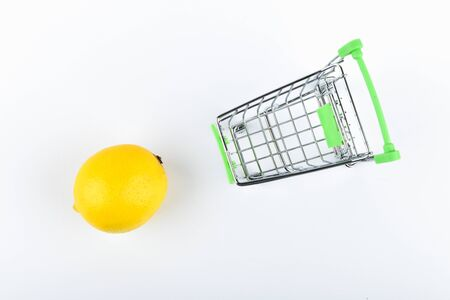 buying lemons. trading concept. Online shopping concept. Cart and lemons over a white background. business concept. Healthy eating concept.
