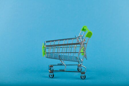 Shopping trolley on a blue background. Green color. Place for an inscription. Shopping concept