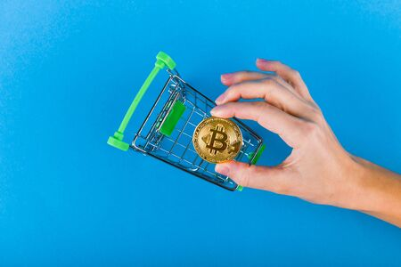 A hand puts bitcoins in a basket. on a dark blue background. place for writing.