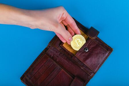Bitcoin theft concept. A hand steals bitcoin from a wallet. Place for writing Stockfoto