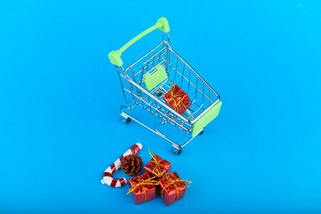 New Years gifts concept. Basket and christmas accessories. Christmas Shopping Cart With Gifts
