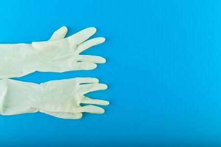 White gloves on a blue background. White latex gloves with a blue background. View from above.