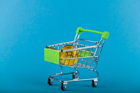 Bitcoin in a shopping cart. On a blue background. place for an inscription