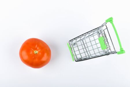 buy tomatoes. shopping concept online store concept. Cart and mandins over a white background. business concept. Healthy eating concept.
