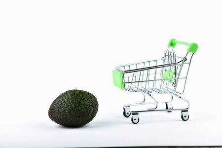 Buying Avocados trading concept. Online store. Cart and avocado over a white background. business concept healthy eating concept.