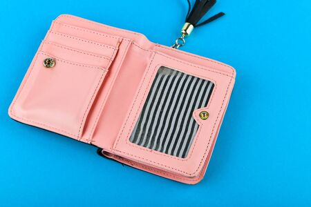 Pink wallet on a blue background. Wallet with a black tassel. A place to write. Close-up. Pink leather wallet isolated on a blue background. Minimalism
