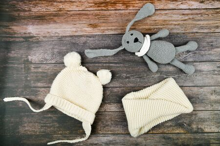 Beige hat with a scarf on a wooden background. Knitted hat and scarf on a wooden table. Top view. Place for writing.