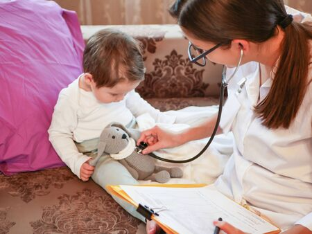 Childrens doctor listens to a child with a phonendoscope. the doctor is at home. call the address. Doctor on call. Phonendoscope, stethoscope. The doctor listens to the breath of a child with a phonendoscope Zdjęcie Seryjne